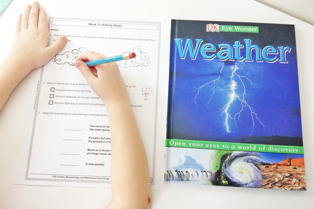 BookShark Science • a child studying weather with a book and activity sheet